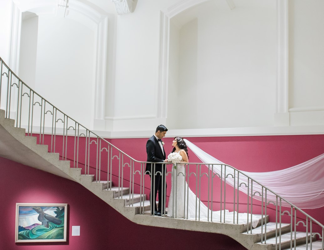 Wedding Couple stand on the stairs of Vancouver Art Gallery by Lestelle Photography