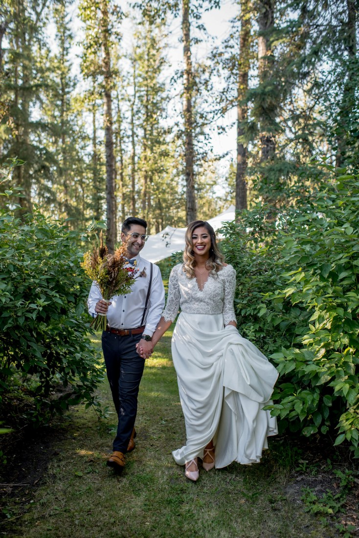 Newlyweds walk through the forest holding hands
