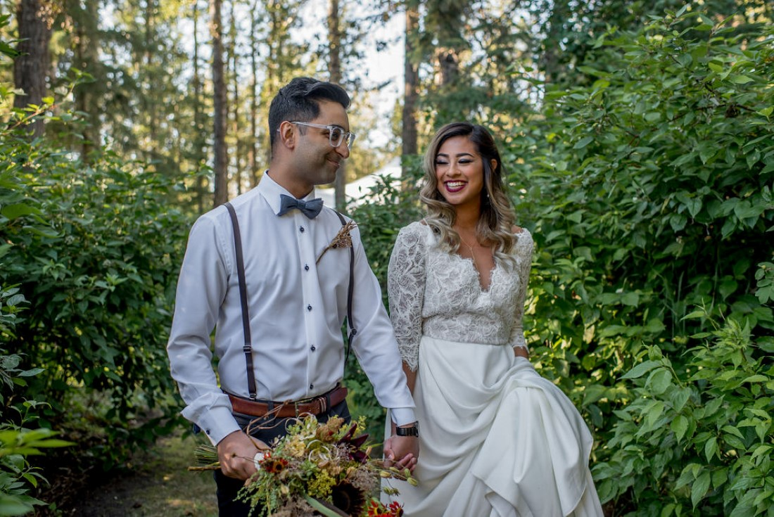 Bride and Groom walk through the woods hand in hand