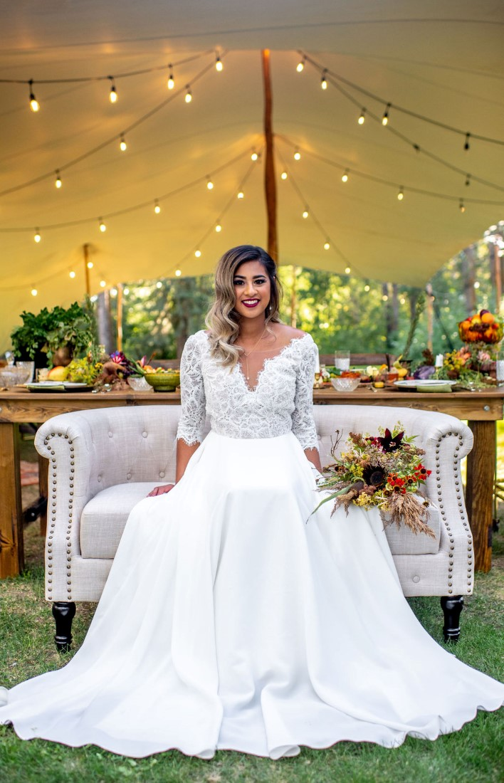 Bride wearing Truvelle gown sitting on settee in field