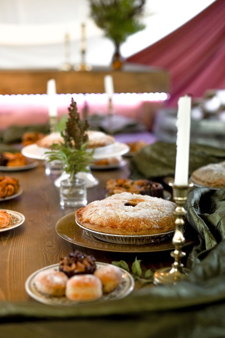 Pie sits on trestle wedding reception table with candles and greenery