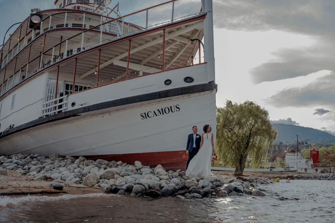 Bride and Groom kiss in front of Sicamous steamship