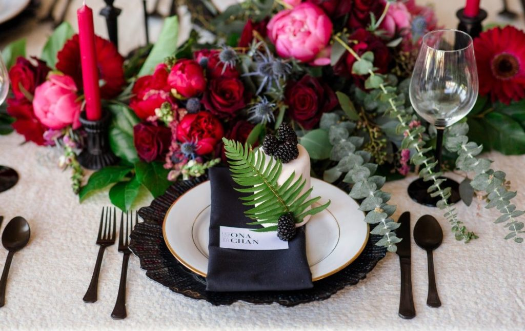 Pink peonies, eucalyptus and fern on black plates on wedding reception table by Thrifty Foods