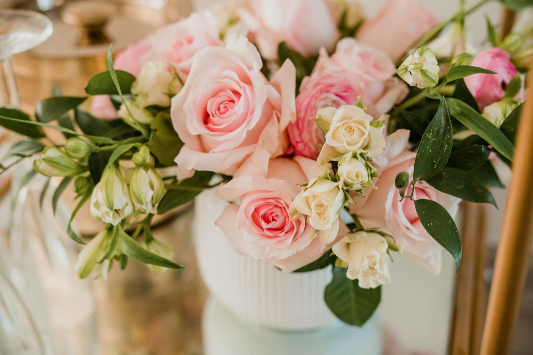 Pink roses in white vase on bridal shower table in Vancouver