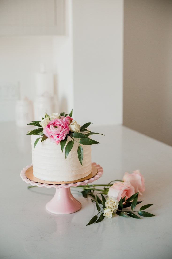 Cake n Sweets Bridal Shower vanilla iced cake on blush pink cake plate with roses and greenery
