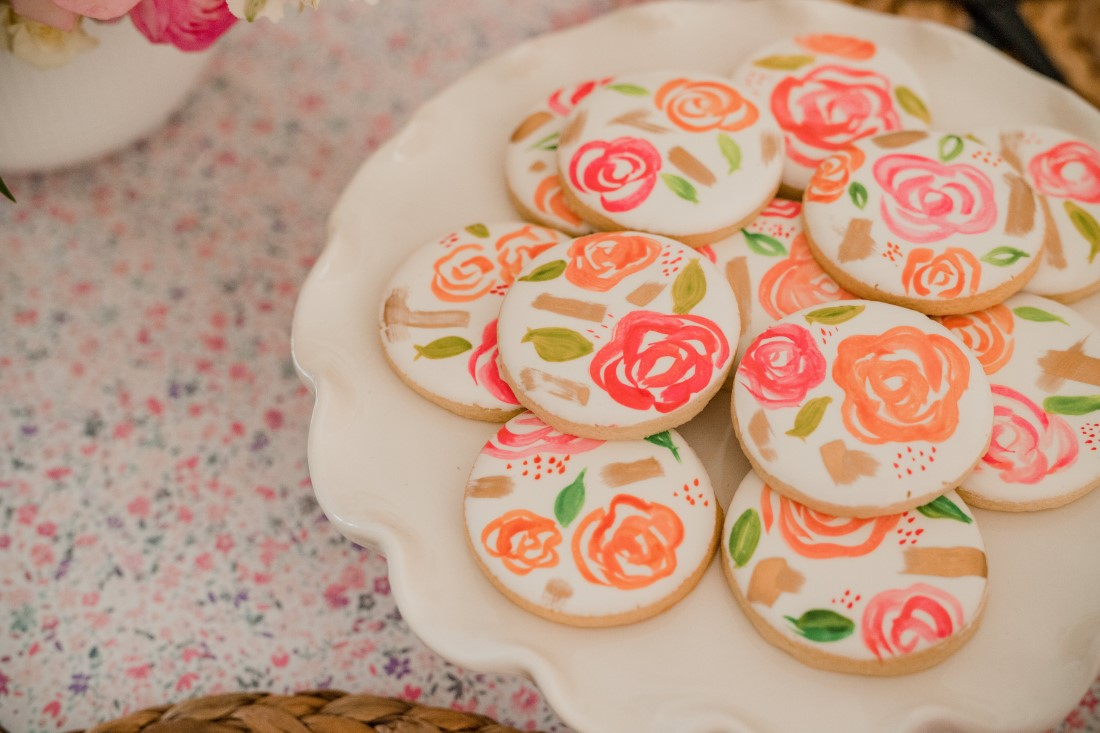 Hand painted cookies with pink flowers on white cake plate by Cake n Sweets Vancouver