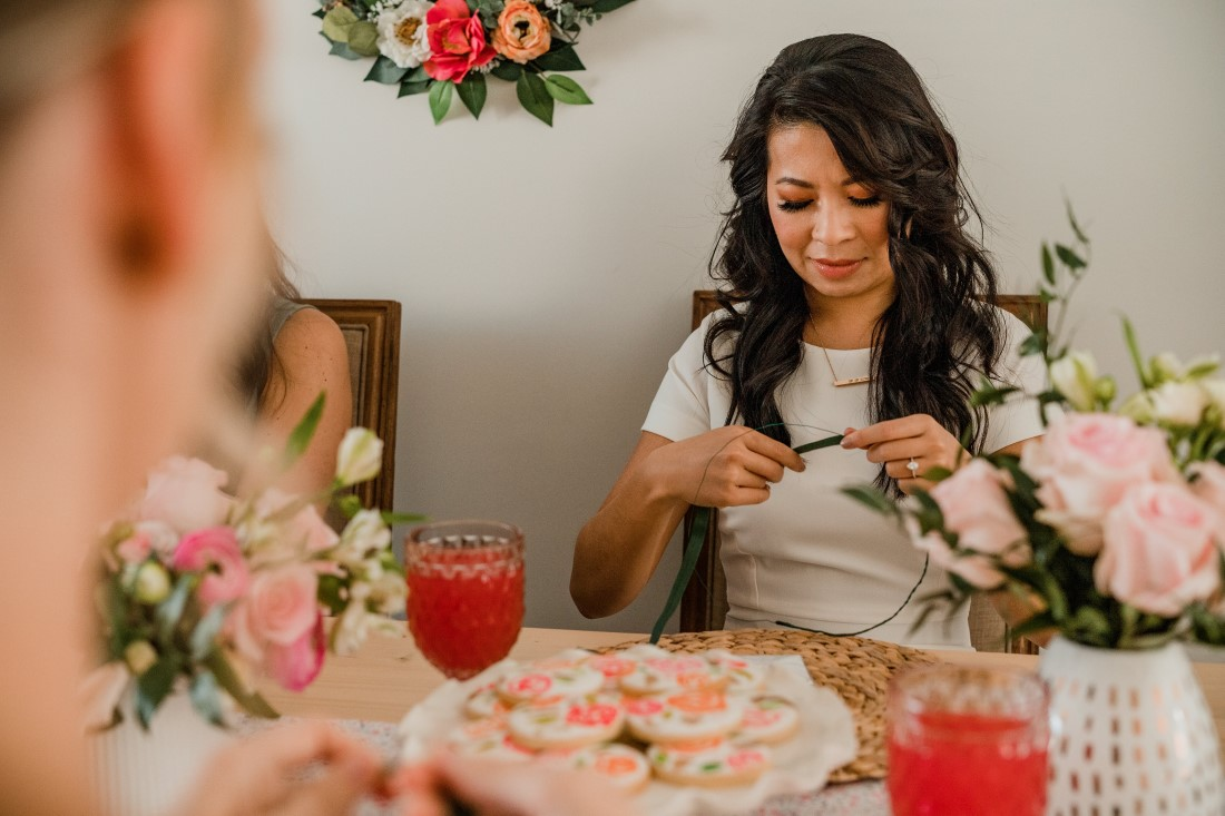 Bride threads flowers on to floral crown at her bridal shower