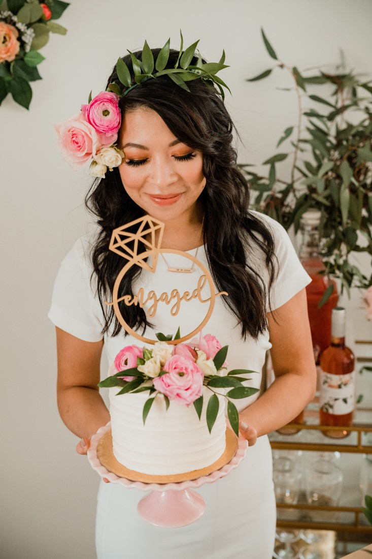 Bride holds shower cake with blush pink flowers and gold topper