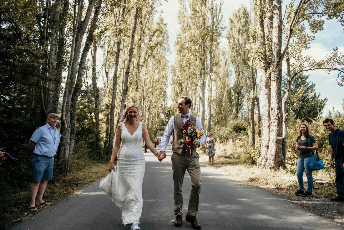 Bride and groom walk towards guests lining sides of road at Covid-19 wedding
