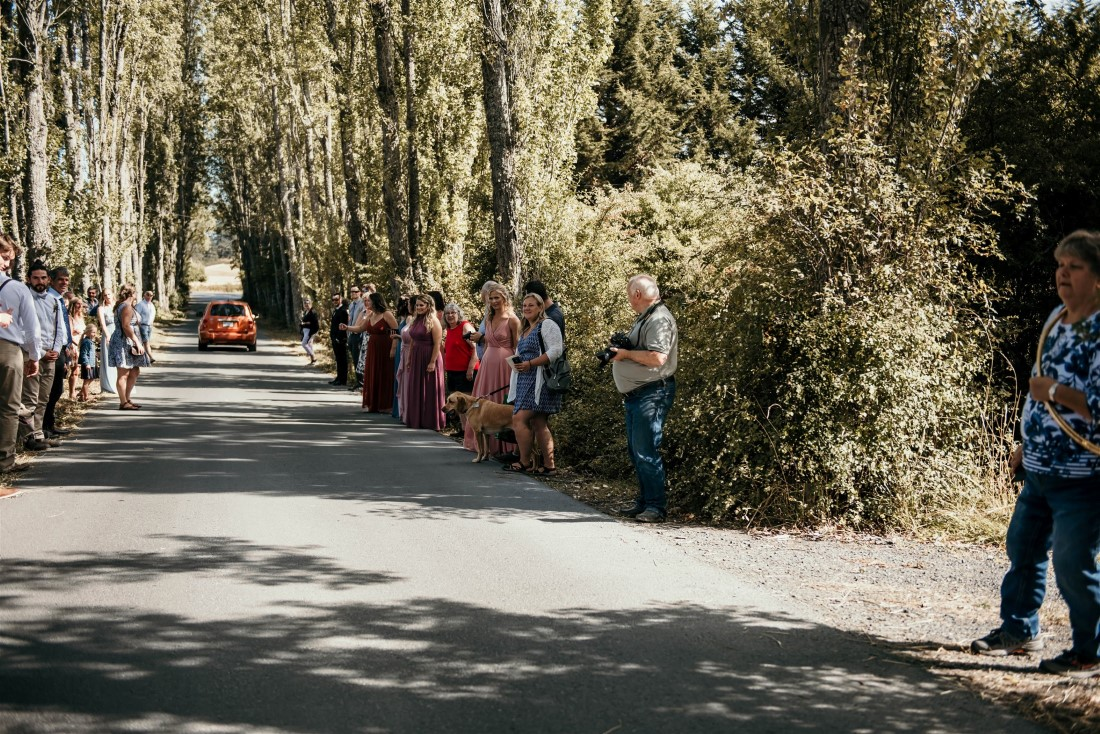 Guests line the road to wave at bride and groom at Covid-19 wedding