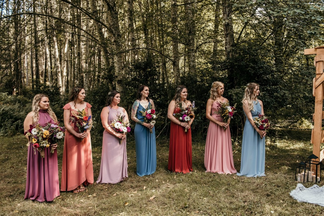 Bridesmaids in multi colored gowns holding wildflowers