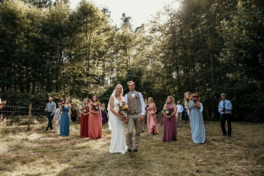 Newlyweds and wedding party in farm field on Vancouver Island