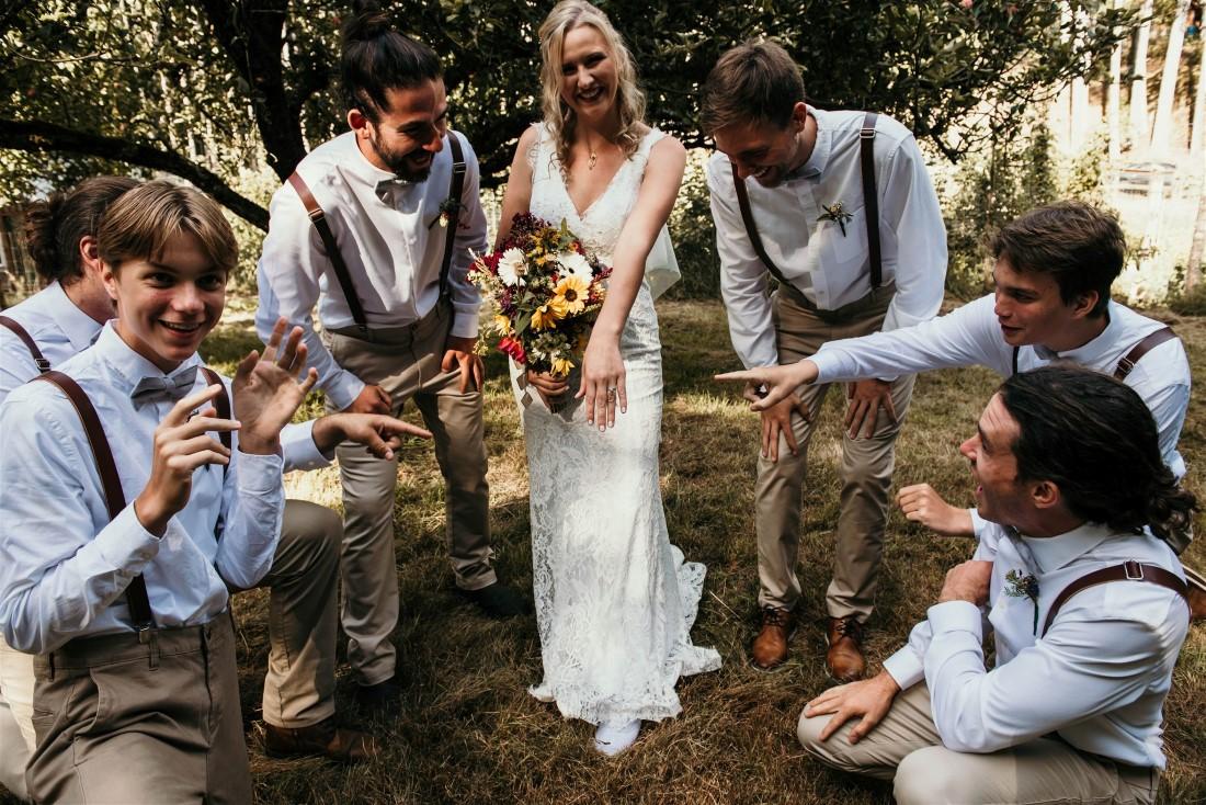Bride surrounded by groomsman wearing brown tweed vests