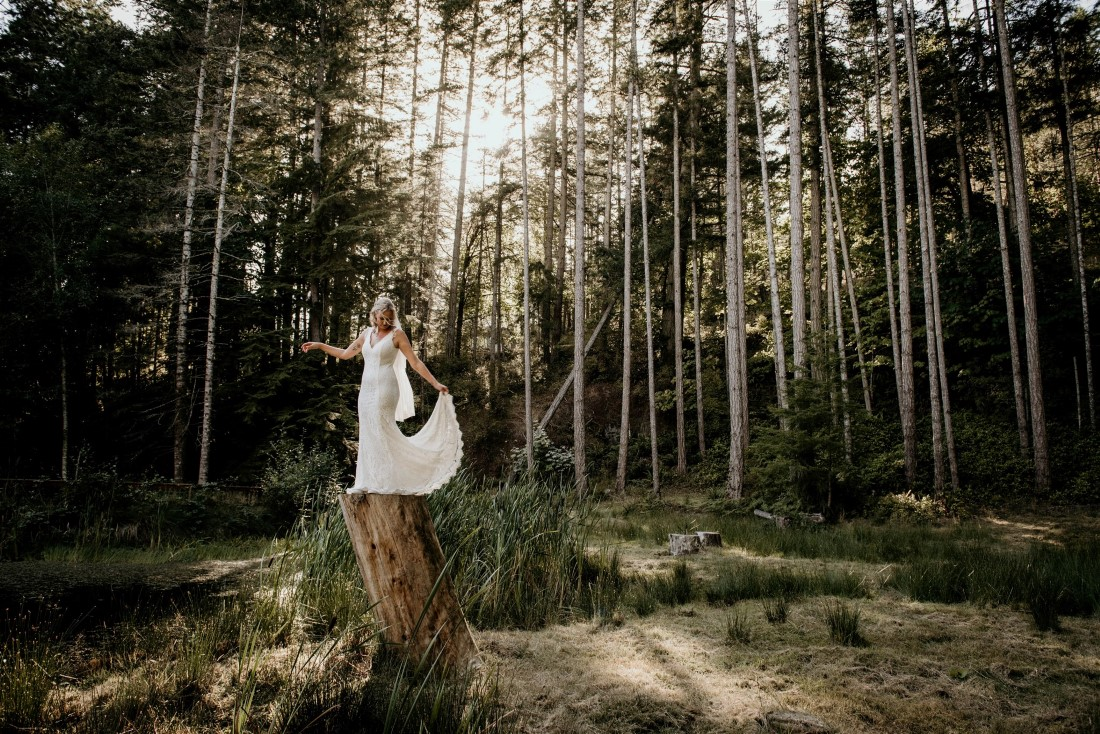 Bride poses on tree stump in BC forest by Coastline Living Photography