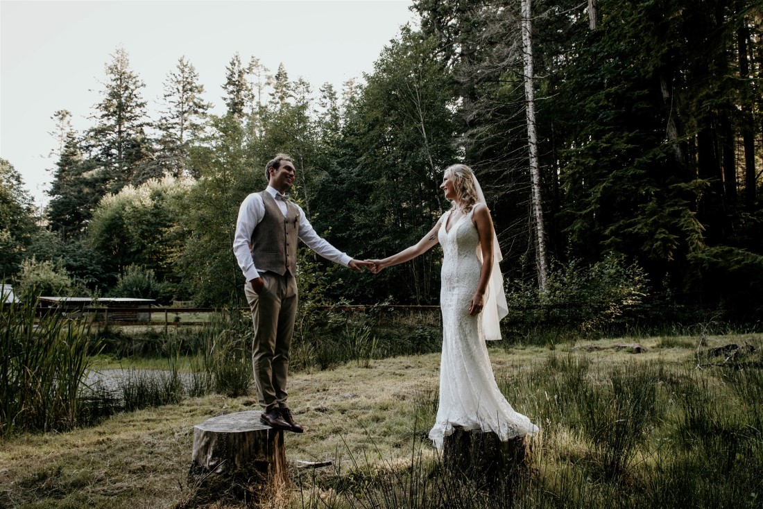Bride and groom stand on tree stumps in Vancouver Island forest