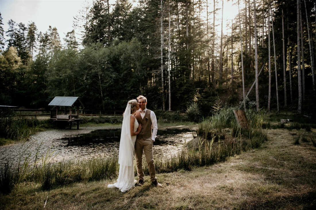 Newlyweds stand in the setting sun in Vancouver Island forest