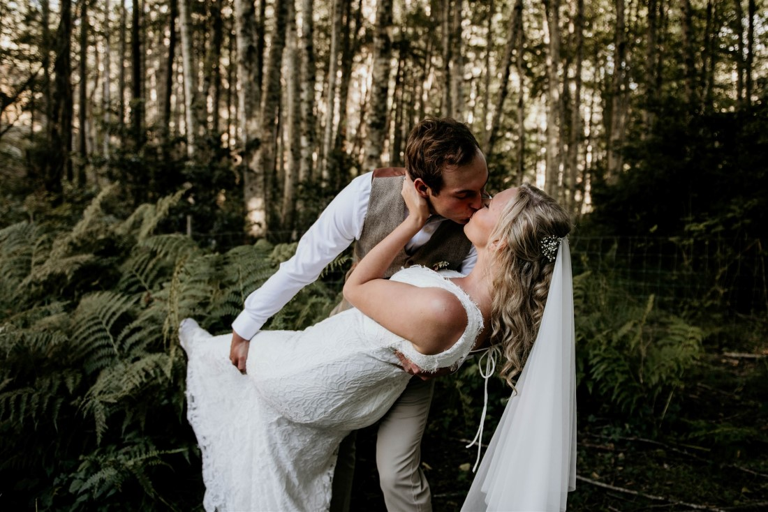 Groom kisses bride in forest on Vancouver Island