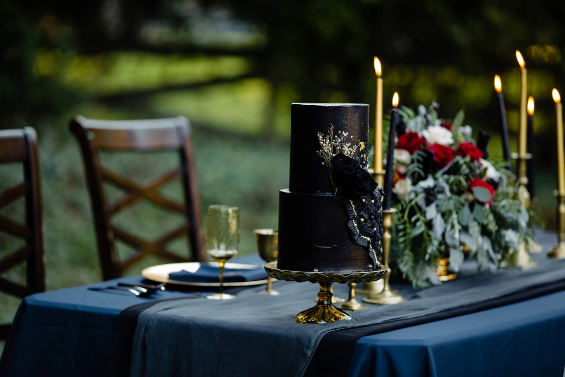 Sweetheart Wedding table with black wedding cake, gold candlesticks and navy linen outdoors in Vancouver