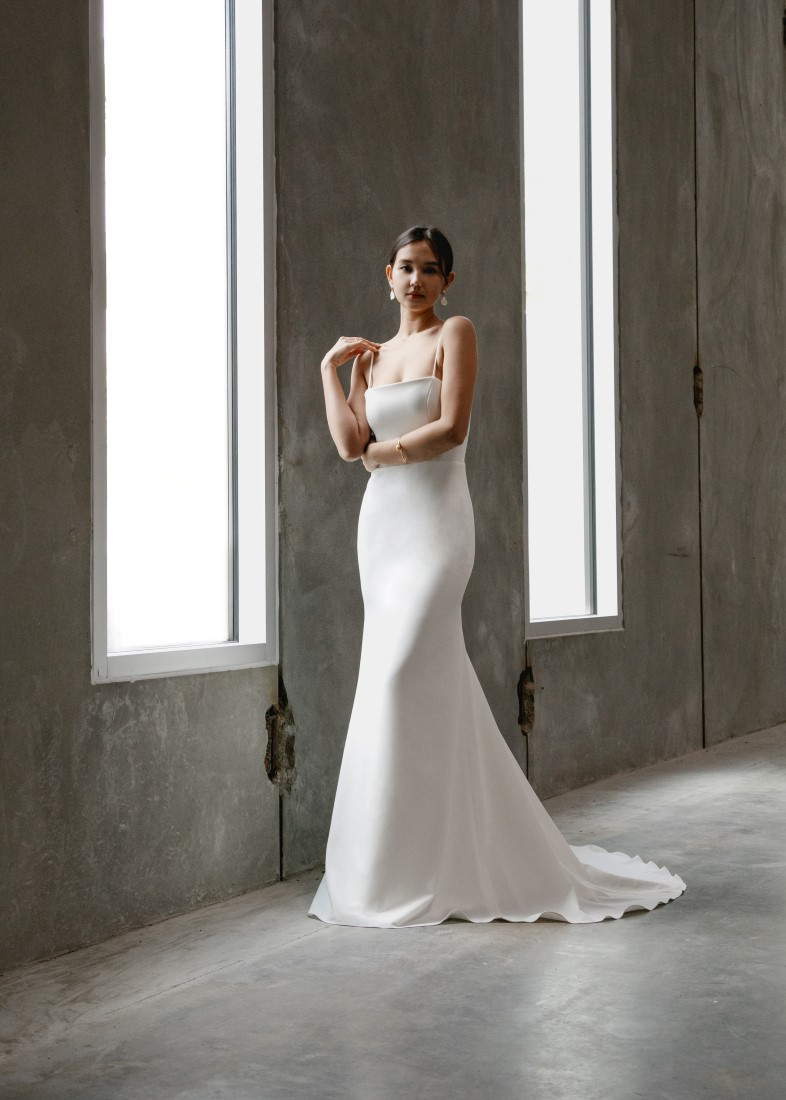 Aesling Crepe wedding dress with a straight-across neckline and spaghetti straps. The back dips into a scoop with a zip up back, and the skirt is a form-fitting mermaid shape Vancouver
