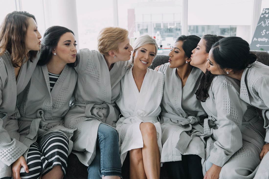 Bride and wedding party hug while getting ready with style in Vancouver
