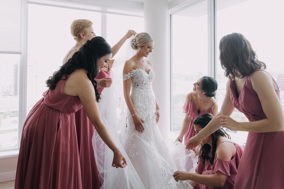 Bridesmaids wearing blush pink gowns help the bride with finishing touches while getting ready in Vancouver