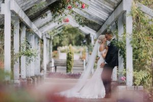 Stanley Park Wedding couplelean against pavilion beam and kiss with roses around them