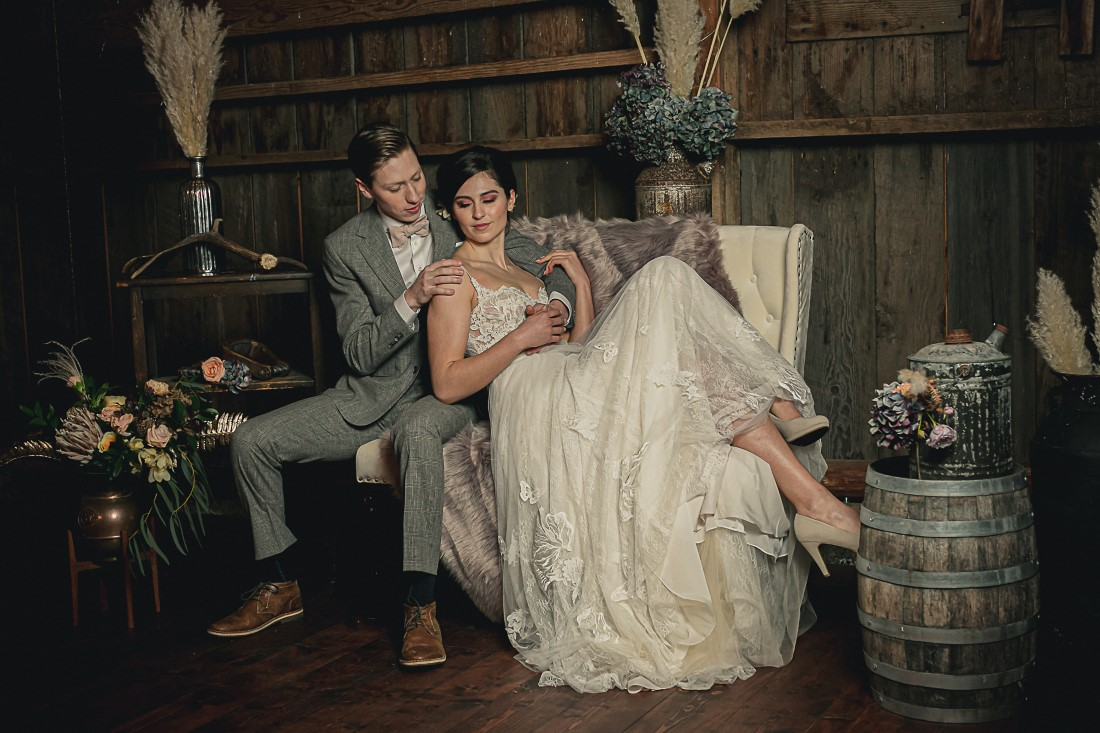 Bride and Groom on settee surrounded by antique wood, barrells, pampas grass and flowers at Langtry Walk