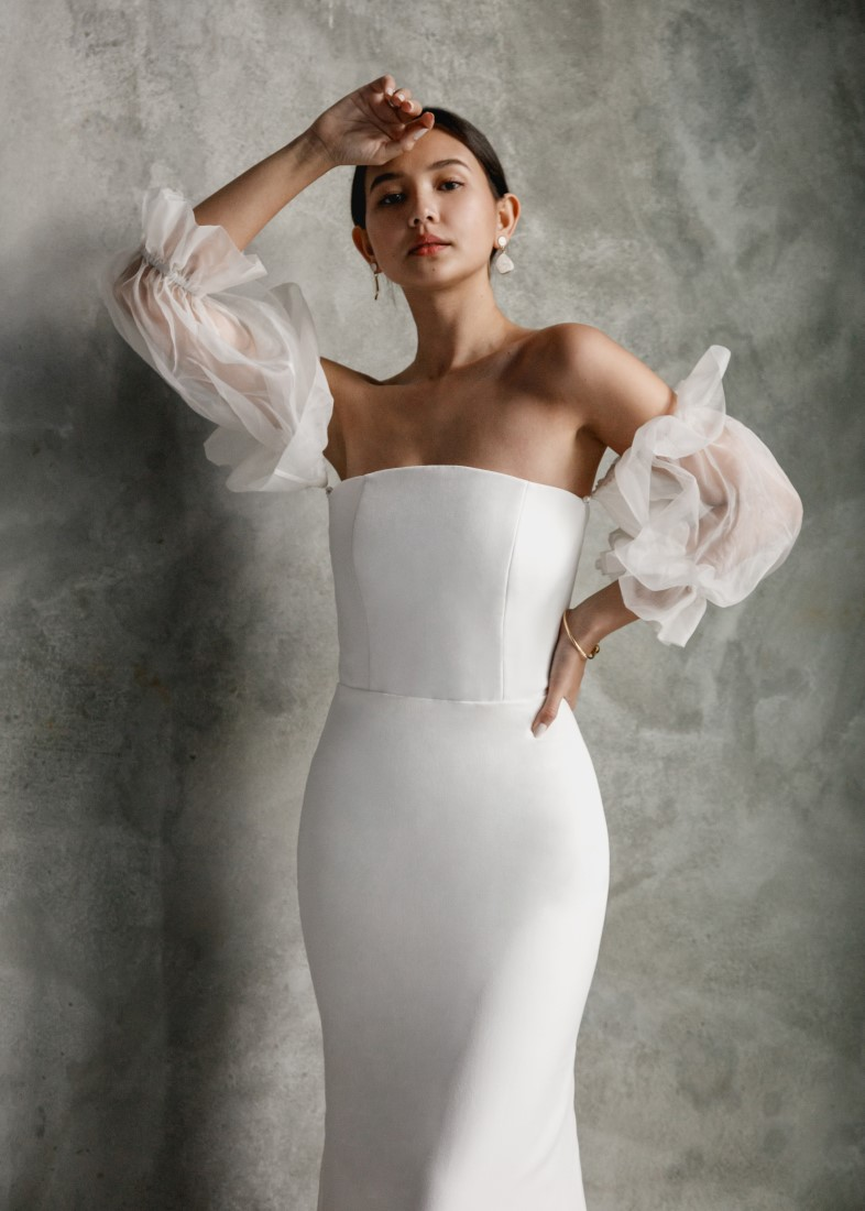 Aesling strapless crepe wedding dress with silk organza puff sleeves and a mermaid skirt. The structured bodice has a zipper back and each puff sleeve is secured with a pearl button.