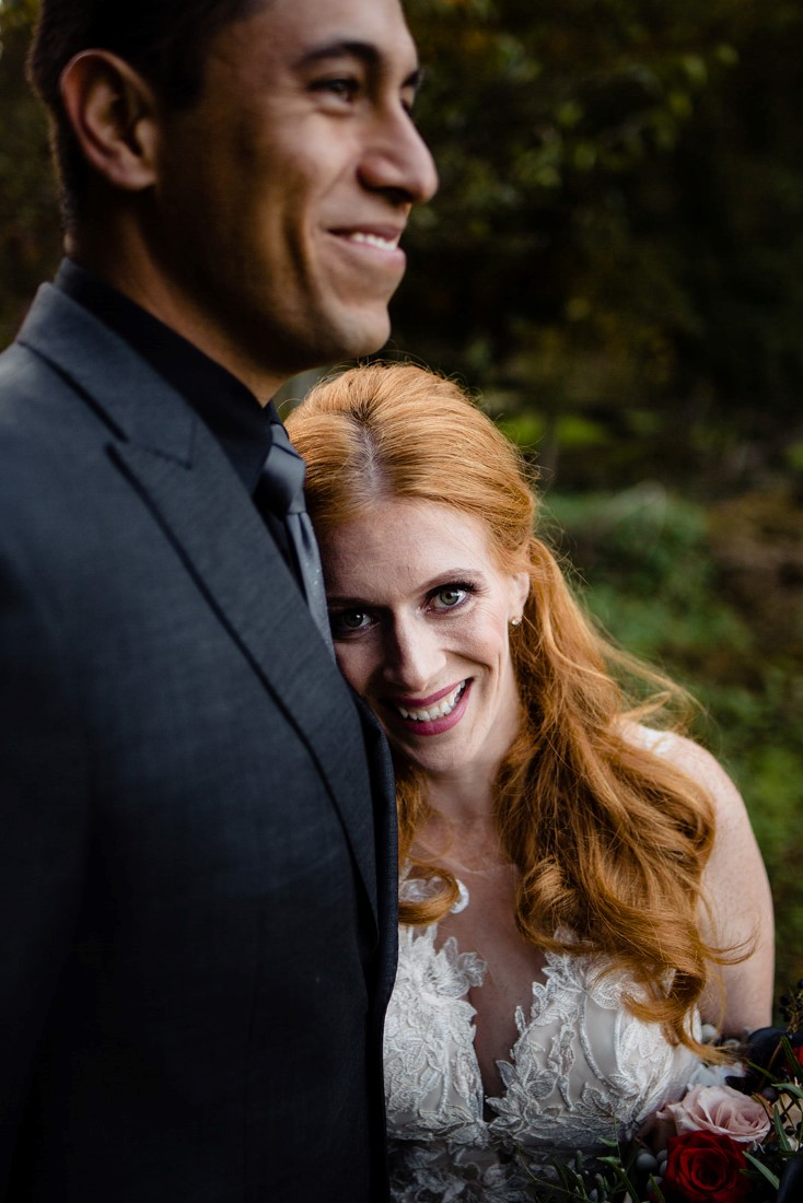 Red Headed Bride smiles while leaning on her groom by Mimsical Photography