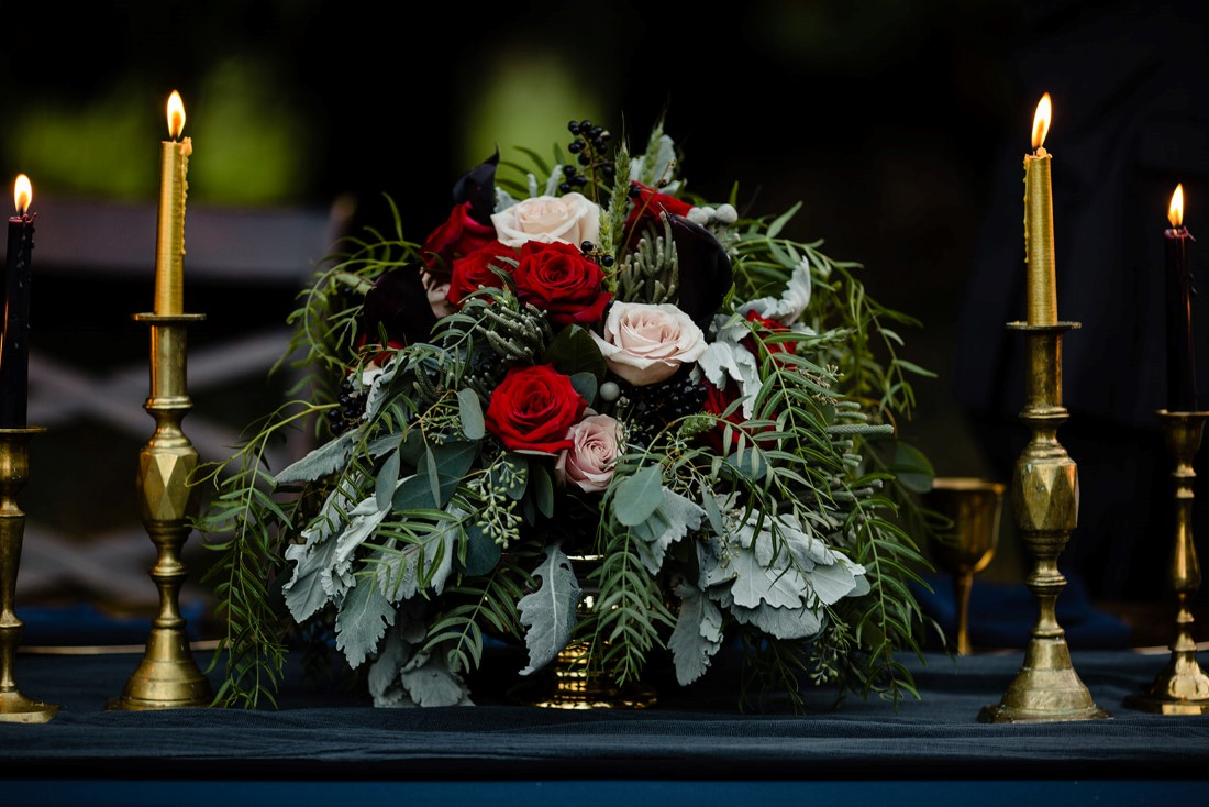 Red Roses, White Roses and Dusty Miller bouquet on wedding reception table
