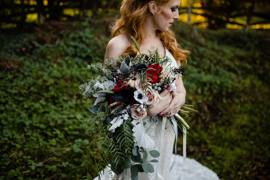 Bride holds bouquet in her arms filled with anemone, roses and dusty miller in Vancouver