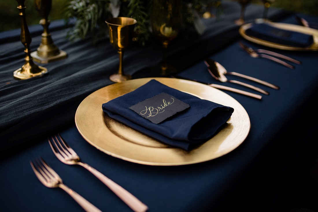 Gold plate and cutlery on black linen with napkin and place card by Pretty Things Rental Vancouver