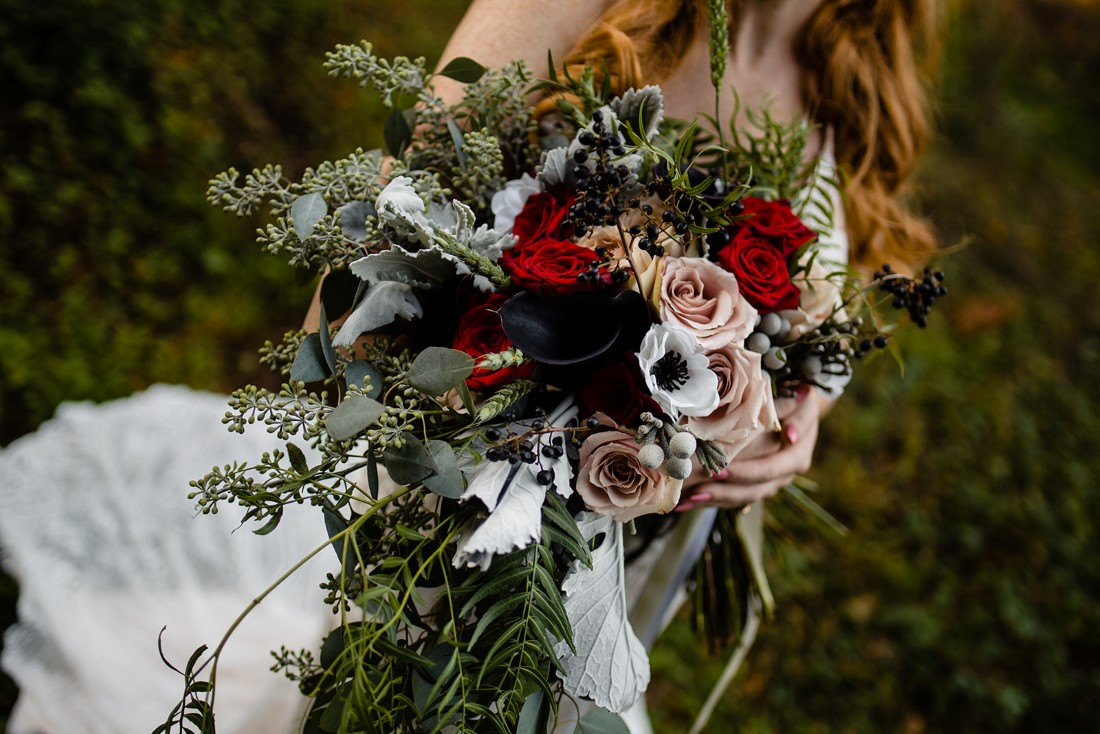 Bridal bouquet with white anemone, red roses, white roses, dusty miller and blue thistle by Edelweiss Floral Vancouver