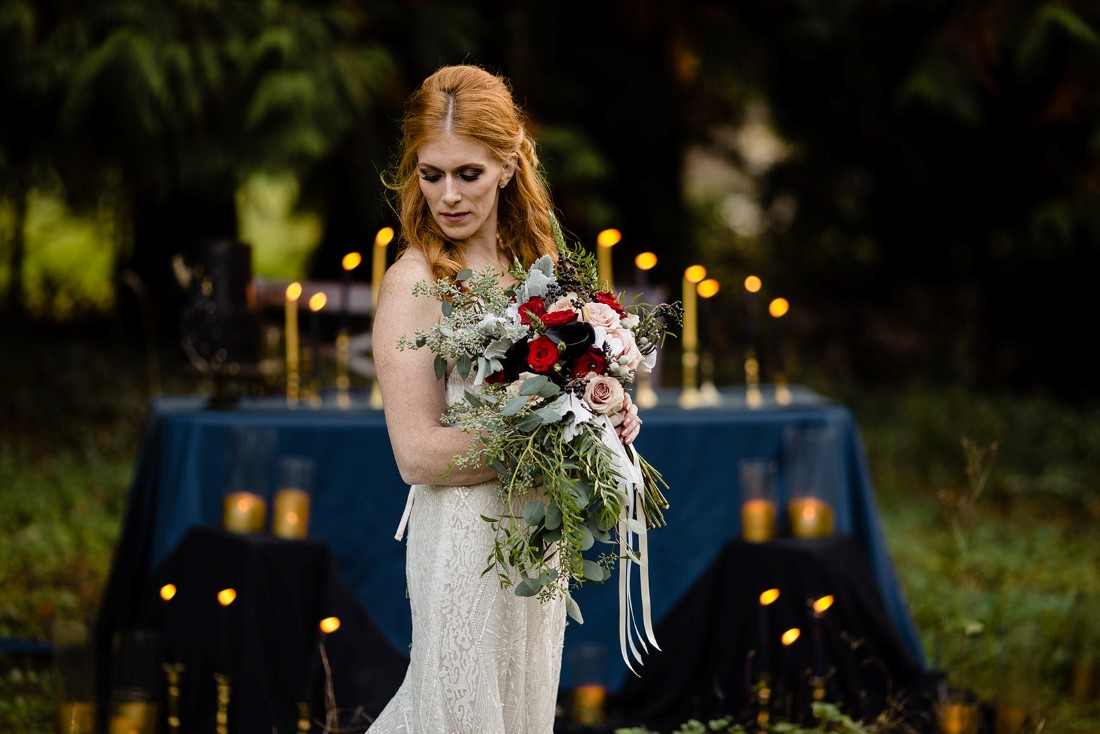 Fall Hues Bride in front of table full of candlesticks by Three Cheers Events Vancouver