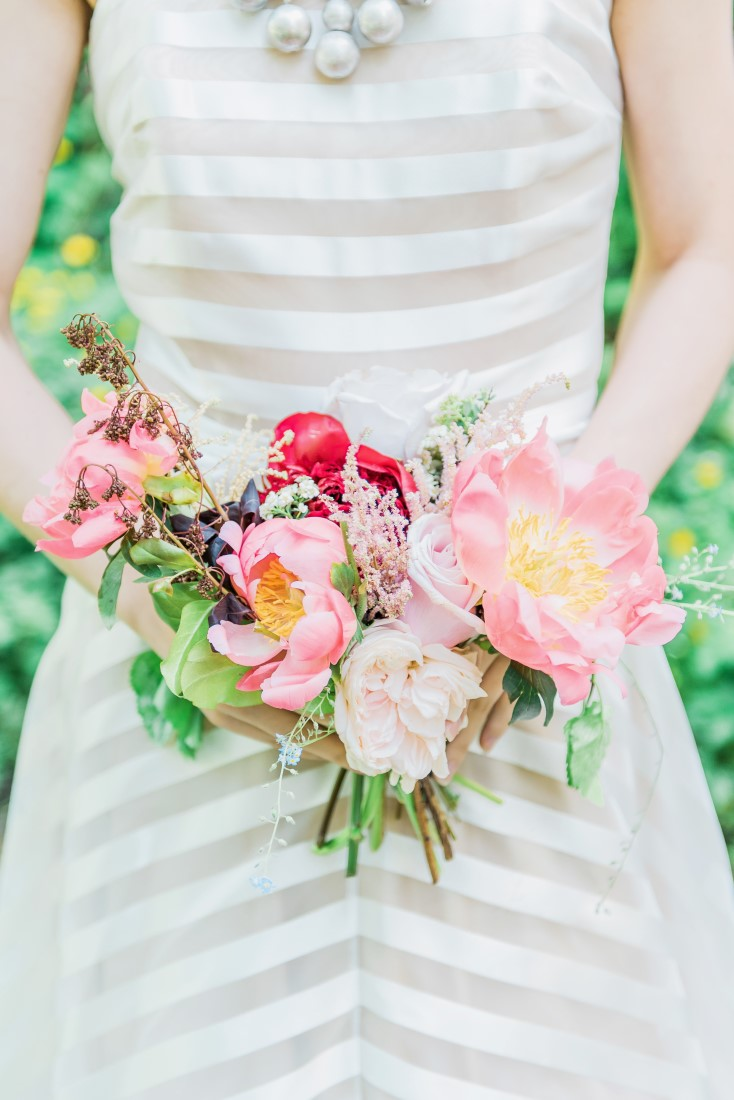 Bridal bouquet of pink peony, white roses against grey and white striped gown by Majesty Bespoke Vancouver