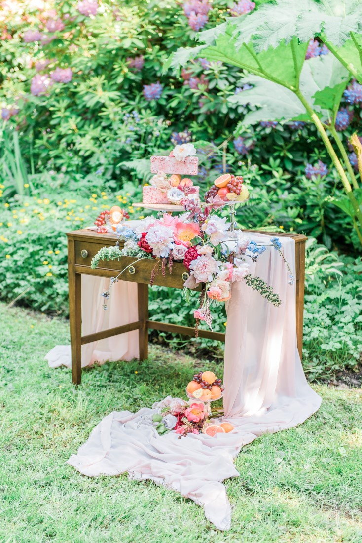 White fabric pools off sweetheart wedding table filled with cakes and flowers in Vancouver park