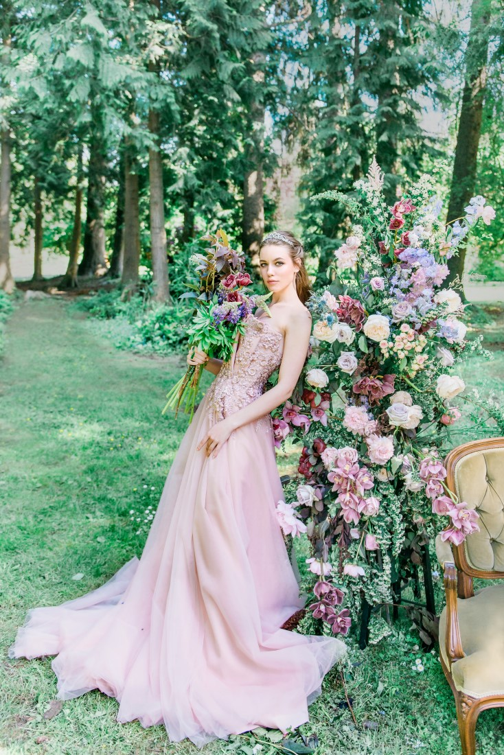 Bride wearing blush pink Majesty Bespoke wedding gown leans against flowers in Vancouver garden