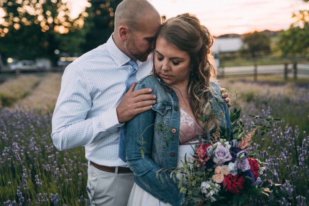 Bride in jean jacket holding bouquet and groom wearing white shirt
