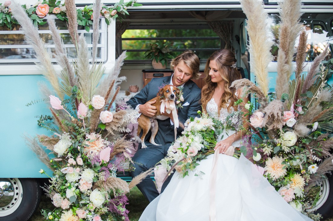 Volkswagon Photobus Elopement couple with dog and surrounded by flowers in Vancouver