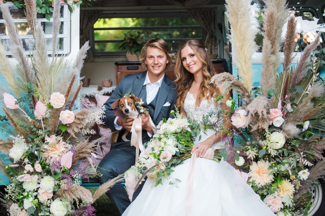 Dog sits on newlyweds who are surrounded by wedding flowers