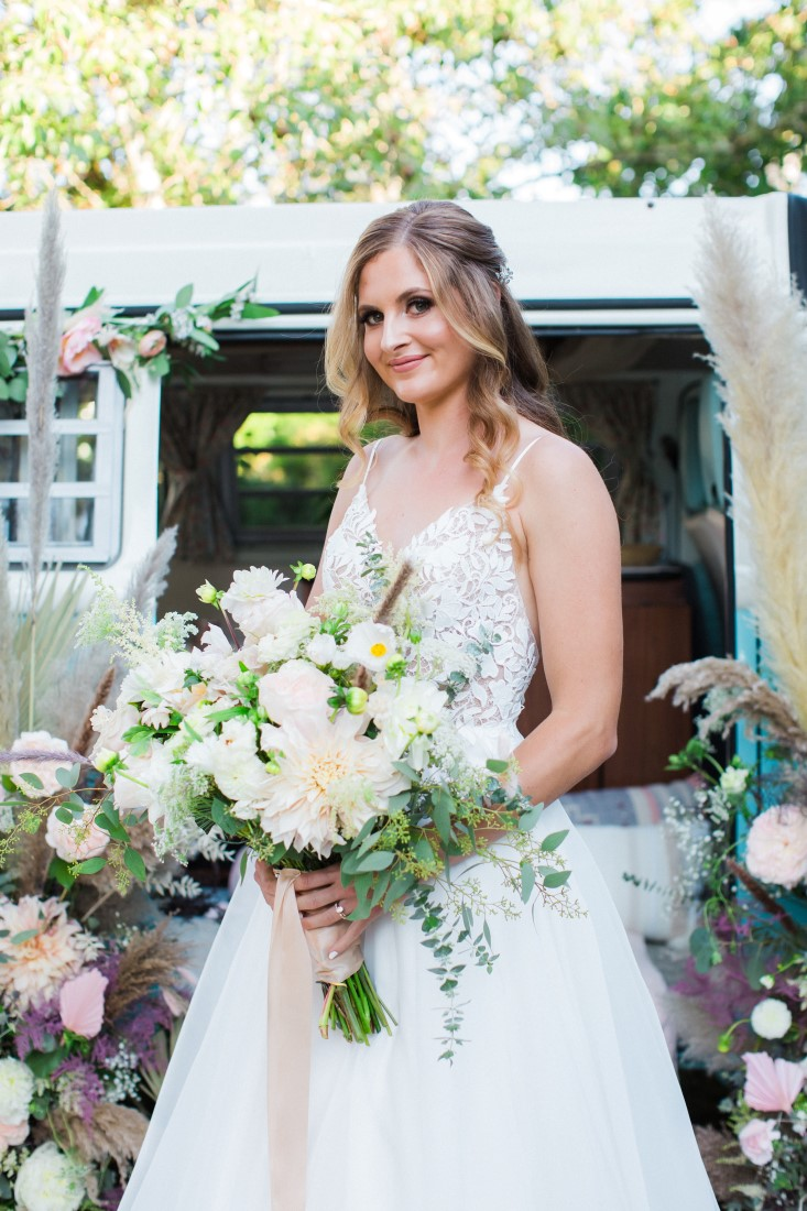 Bride holds large white floral arrangement by Denise Lin Photography