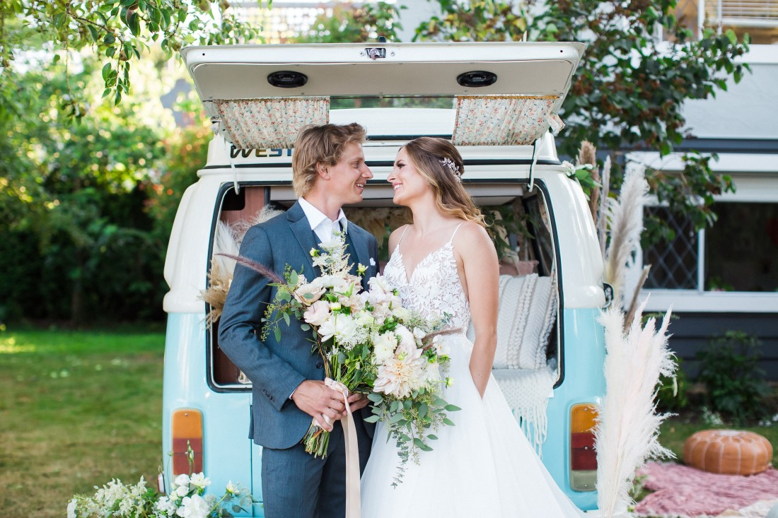 Wedding Couple Stands at back of blue and white Volkswagen van