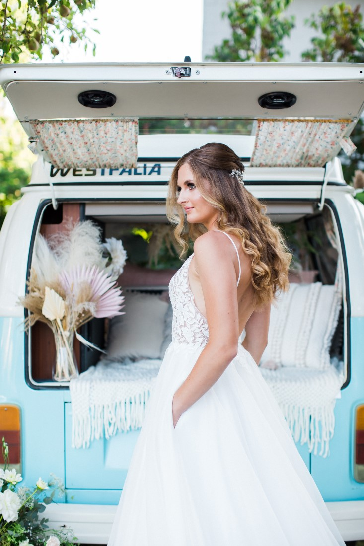 Bride with hands in the pockets of her wedding gown in front of blue and white Volkswagen Van in Vancouver