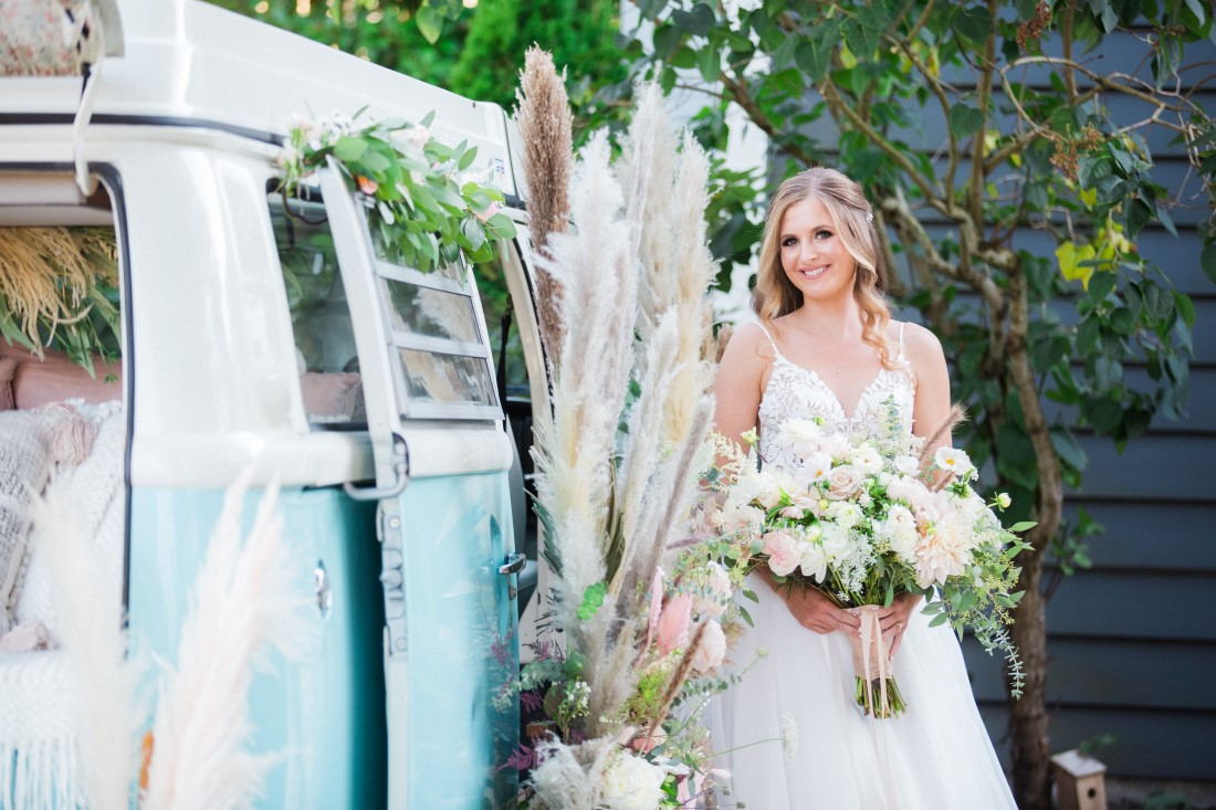 Bride in front of blue and white Volkswagen van with pampas grass