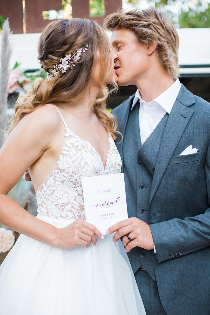 Bride and groom kiss while holding sign We Eloped Vancouver
