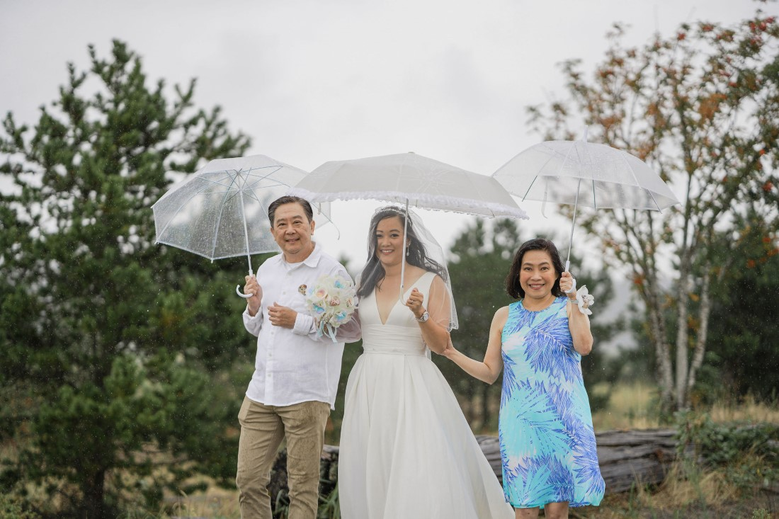 Bride walks down the aisle between her parents and holding umbrellas