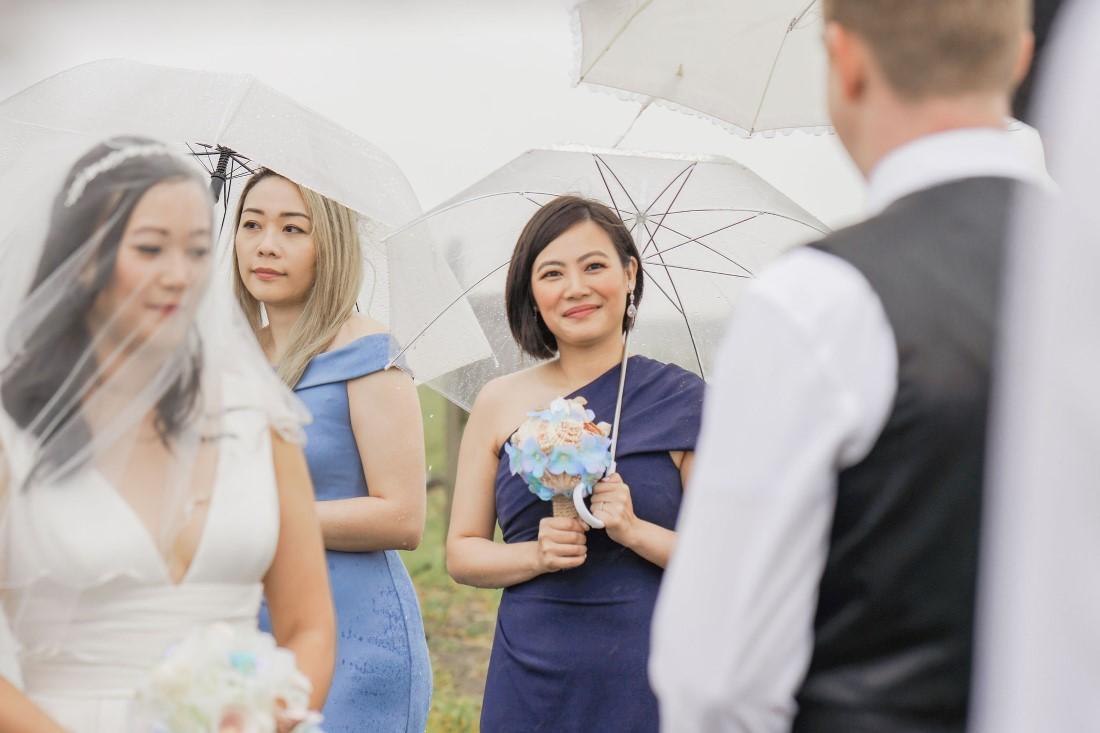 Bride arrives at beach ceremony under bridesmaids umbrellas