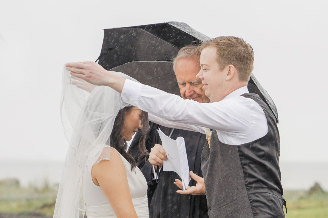 Groom pulls back bride's veil at Vancouver beach ceremony in the rain