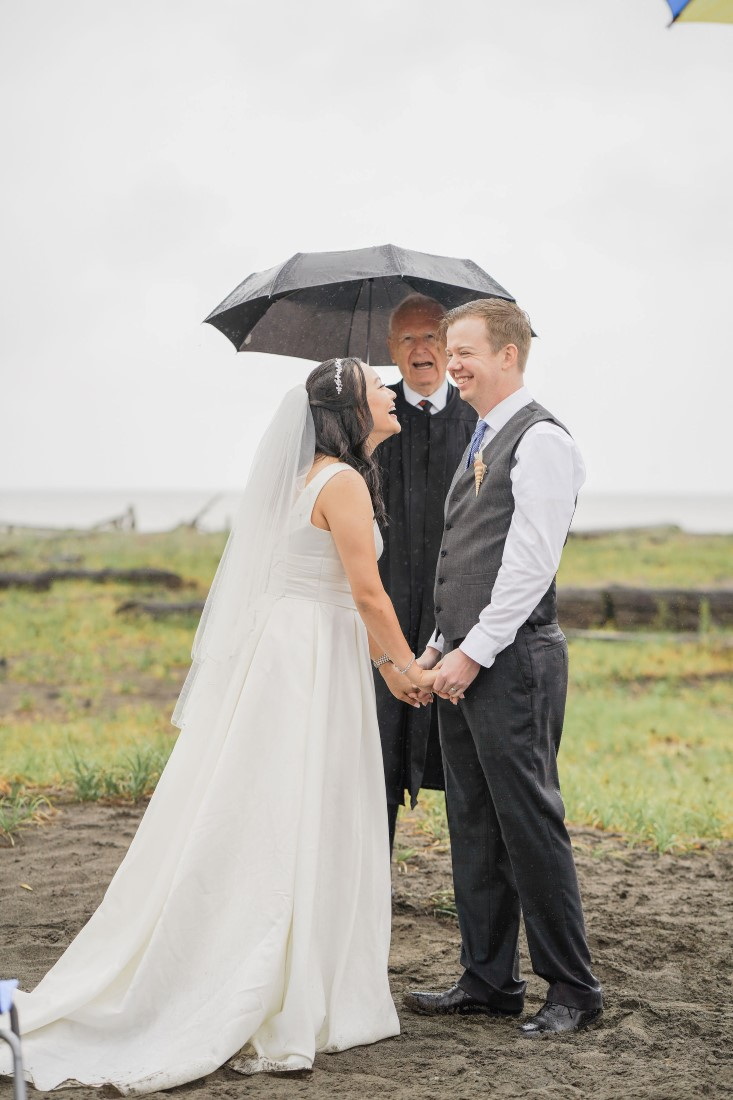 Bride and Groom seal their vows with a kiss under a black umbrella in Vancouver