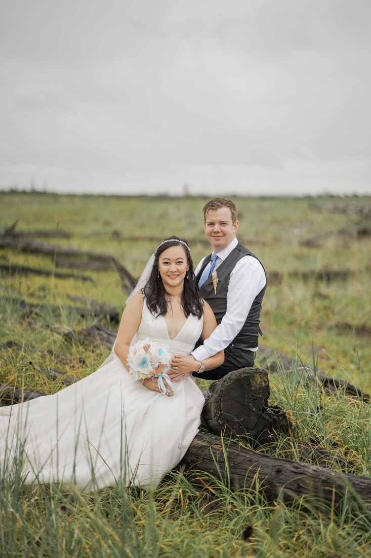 Bride and Groom sit in grassy field near Vancouver